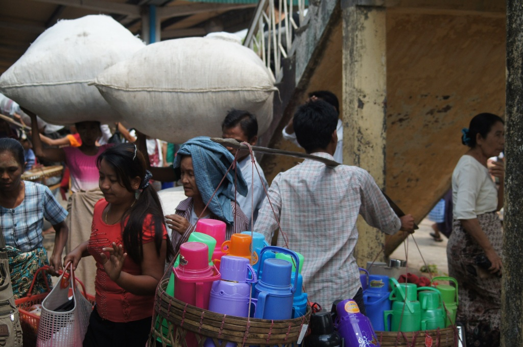 Hawkers on a rail station in Yangon. It remained a mystery what is inside those huge bags.