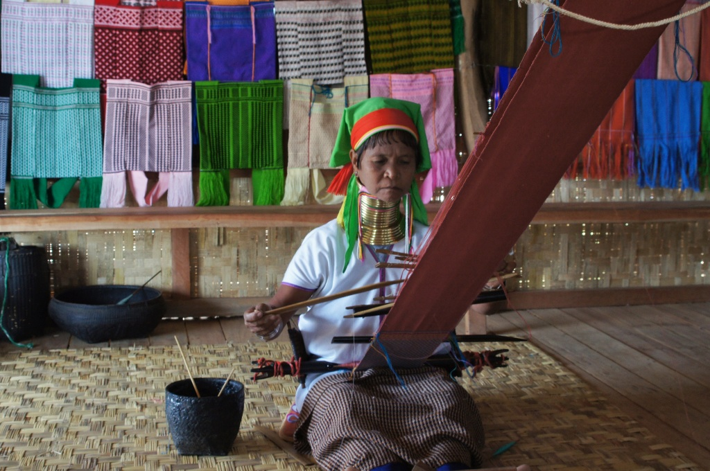 A long-neck woman from Kanyin state demonstrating her weaving skills in one of the shops.